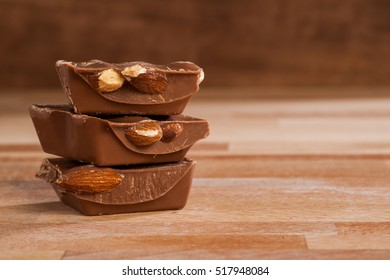 Chocolate with almonds on wooden background