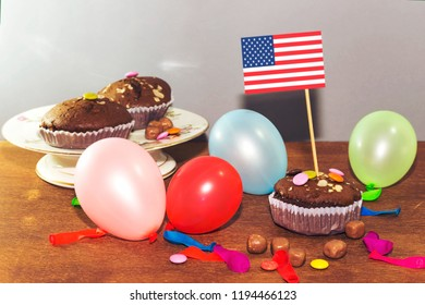 chocolate arabic homemade cupcake, madeleine with colorful ballons and smarties. concept of Columbus day