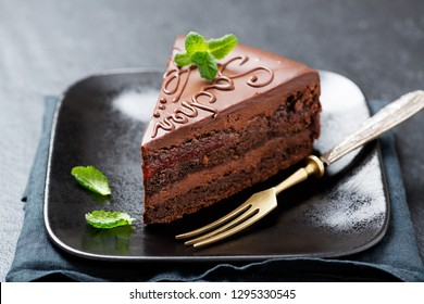 Chocolate Austrian dessert Sacher with apricot jam and mint leaves.