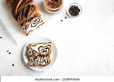 Chocolate Babka or Brioche Bread. Homemade sweet desert pastry - chocolate swirl bread, sliced on white background, top view, copy space.