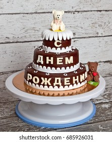 """Chocolate baby cake with the inscription in Russian """"happy birthday"""" on a round plastic stand"""