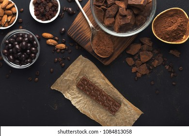 Chocolate background. Milk chocolate bar, bitter chunks, raisins, almonds, cocoa and candies bowls on black table, top view, copy space. Confectionery shop advertising and cooking ingredients concept