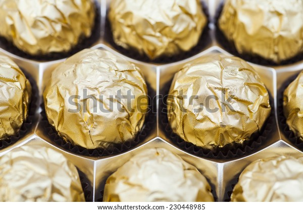 Chocolate balls with almond in gold foil paper