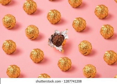 Chocolate balls in gold foil on pink background, pralines in open wrapper foil