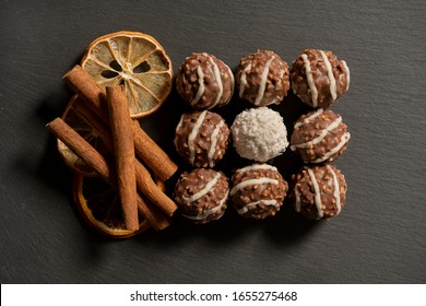 Chocolate balls with nuts and cinnamon on gray background.