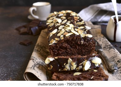 Chocolate banana cake with almond on a dark rustic slate,stone or concrete background.