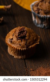 chocolate and banana muffin close up on wooden surface vertical