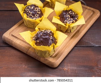 chocolate banana muffins sprinkled with walnut and wrapped in yellow paper on a wooden kitchen board