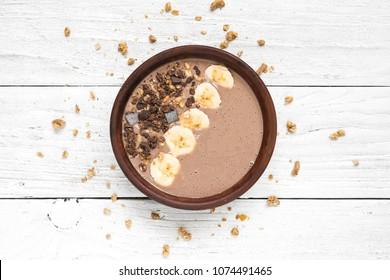 chocolate banana protein smoothie bowl with granola. top view. healthy breakfast