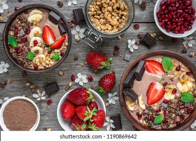 chocolate banana protein smoothie bowls with granola, strawberry, pomegranate and chocolate bars served for breakfast on rustic wooden table. top view. healthy breakfast