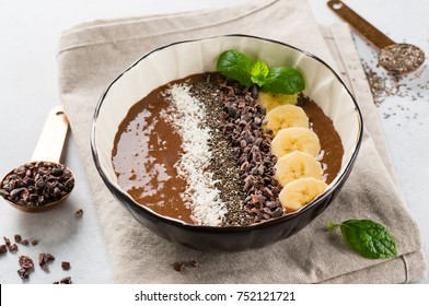 Chocolate banana smoothie bowl topped with cocoa nibs, chia seeds and coconut