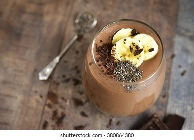 Chocolate banana smoothie with  chia seed on a rustic table.