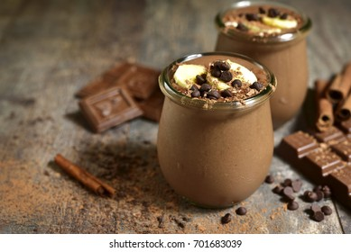 Chocolate banana smoothie with oat and cinnamon in a vintage glass jar on a wooden background.
