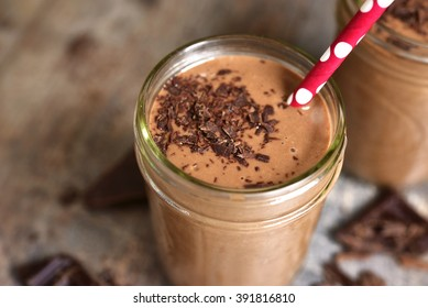 Chocolate banana smoothie on a rustic wooden background.