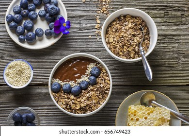 Chocolate Banana Smoothies Bowl with a topping of granola, blueberries, white sesame decorated flowers purple garden viola on simple wooden background. The concept healthy organic breakfast.
