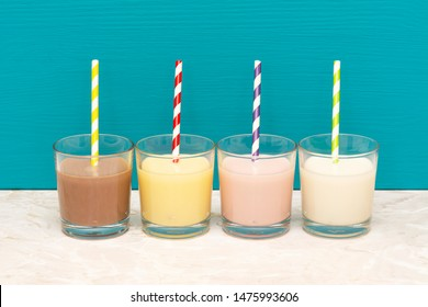 Chocolate, banana and strawberry milkshakes and fresh milk with retro paper straws in glass tumblers with a teal background