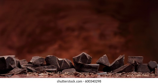 Chocolate bar chunks and pieces on chocolate background