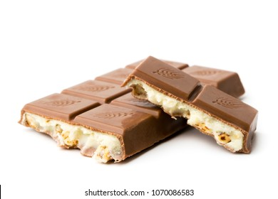 Chocolate bar with condensed milk and nuts broken on a white background.