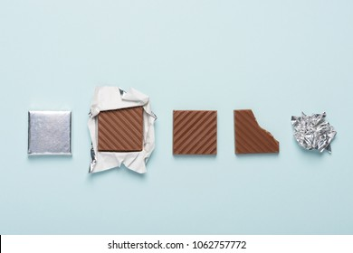 Chocolate bar cycle on blue pastel paper background concept