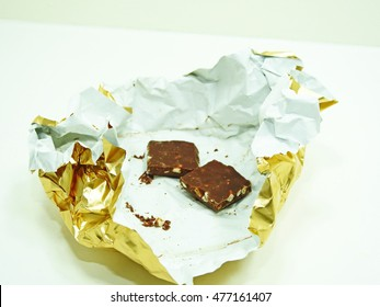 Chocolate bar isolated on white background in golden foil.