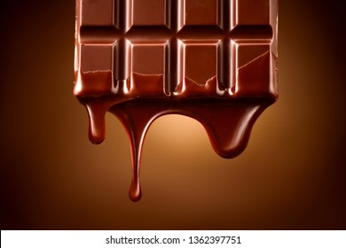 Chocolate bar with melted dark chocolate dripping over dark brown background. Confectionery concept backdrop. Melted premium chocolate flowing. Sweet dessert