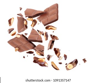 Chocolate bar with nuts broken into pieces in the air on a white background