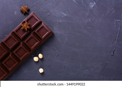 Chocolate bar with nuts on grey background