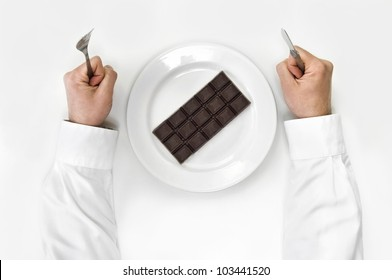 Chocolate bar on a plate and man holding fork and knife isolated on white from top view.