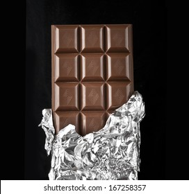 chocolate bar with open cover on dark background