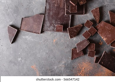 Chocolate bar pieces and  cocoa powder on gray abstract background.