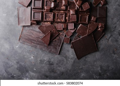 Chocolate bar pieces on gray abstract background.