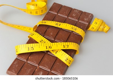 Chocolate bar wrapped with measure tape on gray background