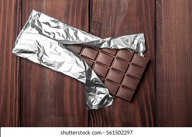 Chocolate bar in wrapper on the dark wooden background. Top view.
