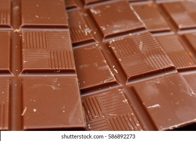 Chocolate bars as background. Milk and dark shiny chocolate texture. Stack chocolates pattern. Stunning beautiful cacao brown dessert sweets.