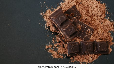 Chocolate bars with word CACAO and cacao powder on black table with space for text,