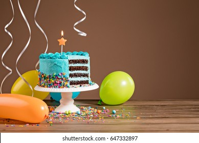 Chocolate birthday cake with blue buttercream icing and colorful balloons on a brown background.