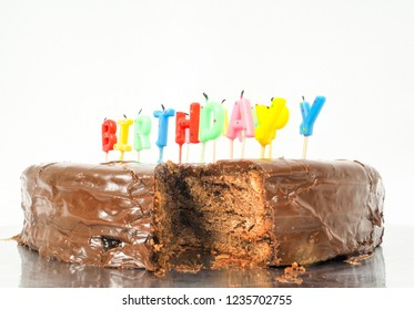 Chocolate birthday cake with candles towards white
