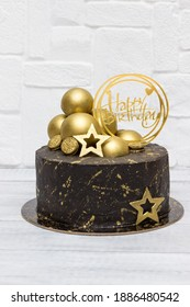 Chocolate birthday cake with gold decor.