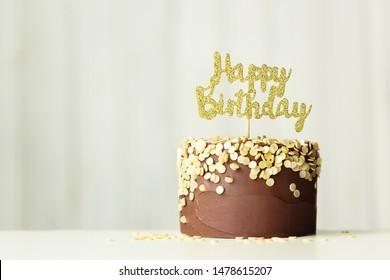 "Chocolate birthday cake with golden ""happy birthday"" sign"