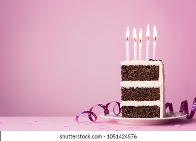 Chocolate birthday cake with pink frosting and candles