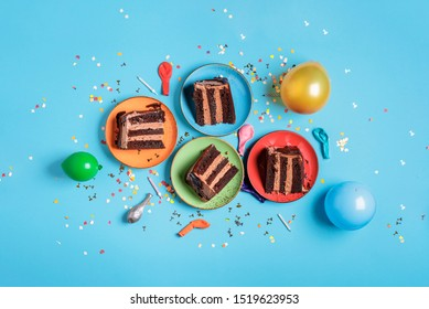Chocolate birthday cake slices on plates, candles, balloons, and confetti on a blue table. Above view of festive dessert. New year celebration concept