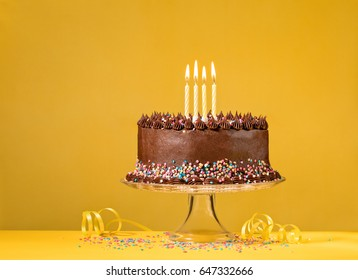 Chocolate birthday cake with sprinkles and candles over yellow background.
