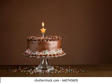 Chocolate birthday cake with sprinkles and candles over a brown background.