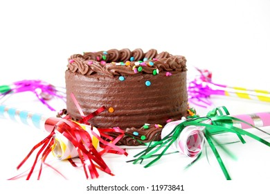 Chocolate birthday cake with sprinkles and noise makers all isolated on a white background