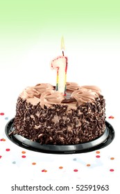 Chocolate birthday cake surrounded by confetti with lit candle for a first birthday or anniversary celebration