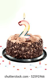 Chocolate birthday cake surrounded by confetti with lit candle for a second birthday or anniversary celebration