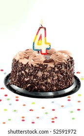 Chocolate birthday cake surrounded by confetti with lit candle for a fourth birthday or anniversary celebration