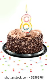 Chocolate birthday cake surrounded by confetti with lit candle for an eighth birthday or anniversary celebration