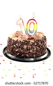 Chocolate birthday cake surrounded by confetti with lit candle for a tenth birthday or anniversary celebration