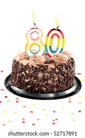 Chocolate birthday cake surrounded by confetti with lit candle for a eightieth birthday or anniversary celebration